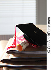 mortar board on stack of files