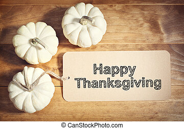 Happy Thanksgiving message with small white pumpkins on...