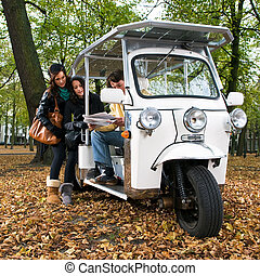 Solar powered tuc tuc - Two women and a driver reading a...