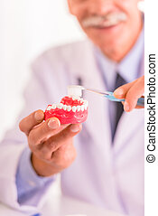Old woman - Caring for your teeth. Dentist teaching to brush...