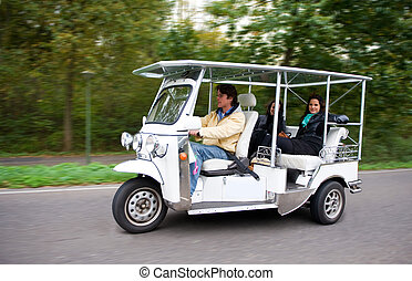 Solar powered tuc tuc driving on a road, with two female...