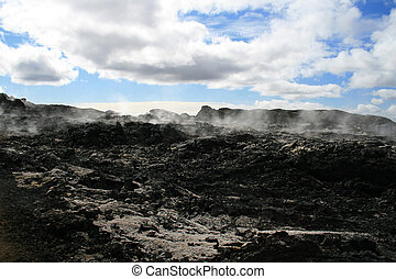 Black lava and steam - black lava field with steam in...