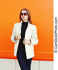 Fashion elegant woman in white coat against orange...
