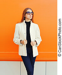 Fashion pretty woman wearing a white coat jacket against...