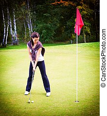 Woman golf player training putting ball on green to cup