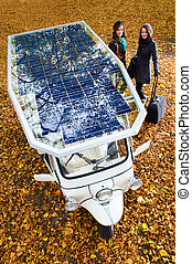 Solar powered tuc tuc - Two young women posing netxt to a...