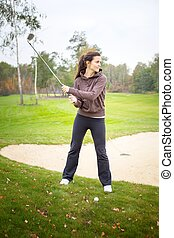Woman player training on golf course, preparing to shot -...