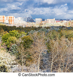 storm clouds over city and first snow on woods in autumn day