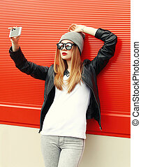Fashion hipster cool girl taking self-portrait on smartphone in city