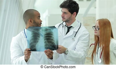 Three confident doctor examining x-ray snapshot of lungs in...