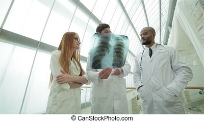 Three confident doctor examining x-ray snapshot of lungs -...