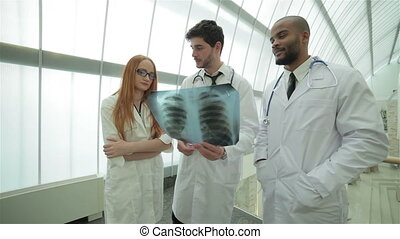 Confident doctor examining x-ray snapshot of lungs in hospital