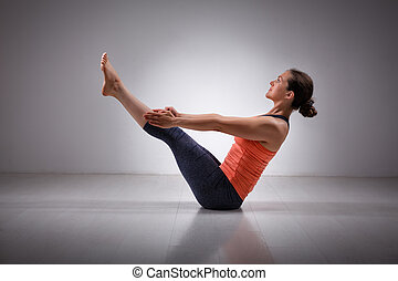 Woman practices yoga asana Paripurna navasana - Beautiful...