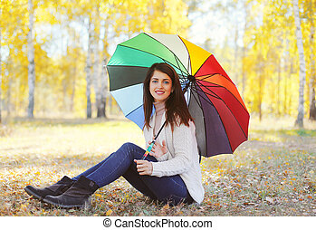 Beautiful smiling woman and colorful umbrella in autumn day