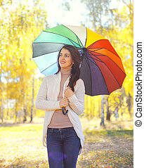 Beautiful smiling woman with colorful umbrella in autumn day