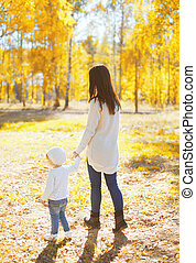 Happy mother walking with child in sunny autumn day