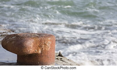 Rusty bollard on pier - Old pier with a rusty bollard ,in...