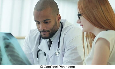 Smiling doctor talking to patient while sitting at a table in the hospital