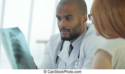 Serious Doctor talking to patient and keeps chest X-ray in...