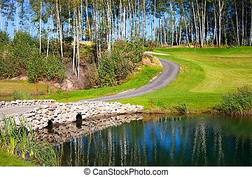 Golf course in autumn, grass field and lake