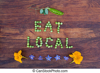 """Sign """"Eat Local"""" made of green peas and pea pod with leaves..."""