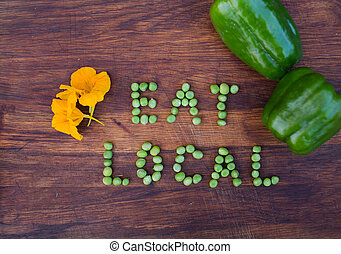 Sign 'Eat Local' made of green peas on wooden background....