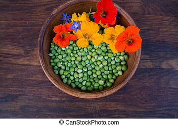 Peas with colorful edible flowers - Green peas and colorful...