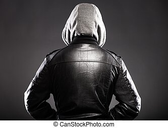 Young man in leather jacket and hood rear view on back