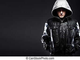Scary hooligan man in leather jacket with a hood