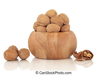 Walnuts in a beech wood bowl and scattered, isolated over...