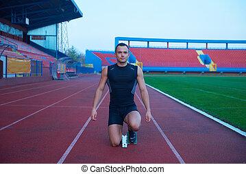 Athletic man start - Sprinter leaving starting blocks on the...