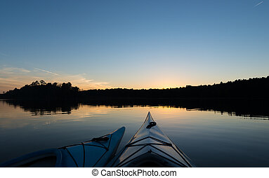 Two Kayaks at Sunset - Two kayaks on a tranquil lake as the...