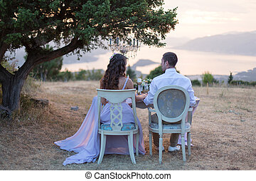 the bride and groom posing at sunset sitting at the wedding...