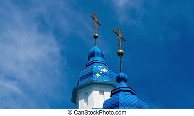 The church against the blue sky and the moving clouds. -...