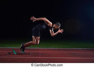 Sprinter leaving starting blocks on the running track....