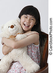 girl hugging teddy bear - chinese girl having fun playing...