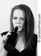 depressed young woman drinking from a wine bottle