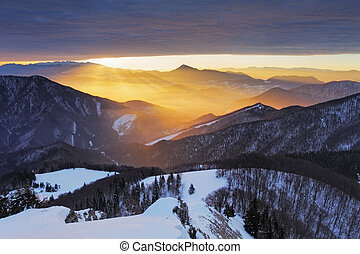 Sunlight rays over mountain at winter
