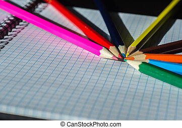 Colored pencils lying on an open notebook