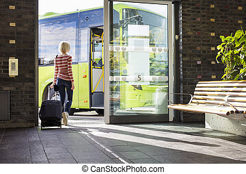 Female traveler going on the bus at terminal - Young woman...