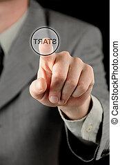 Businessman pressing virtual start button - A businessman...