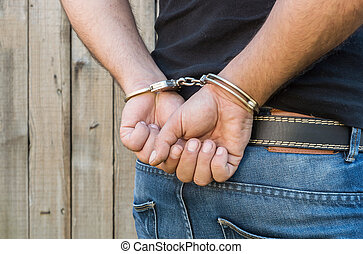 Man with Handcuffs - Arrest, close-up shot man's hands with...