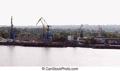 The work of a large crane in the river port - Big blue and...