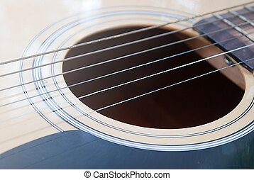 Acoustic guitar, focus on strings above sound hole