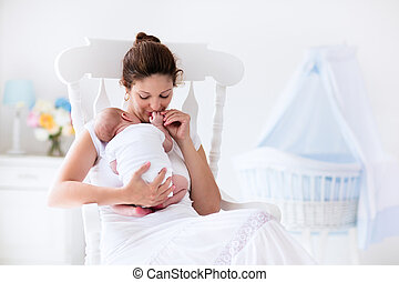Young mother and newborn baby in white bedroom - Young...
