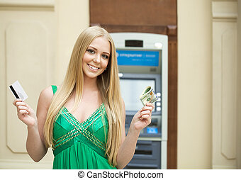 Blonde woman in a green dress is holding a cash dollars -...