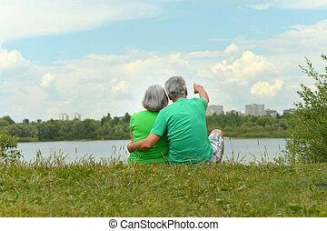 Senior couple sitting near lake - Happy senior couple...
