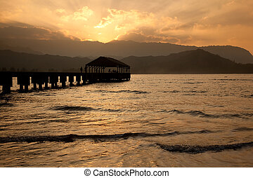 Hanalei Pier at sunset - Sun setting behind Na Pali...