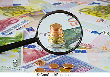 Coin stack behind magnifying glass on a background made of...