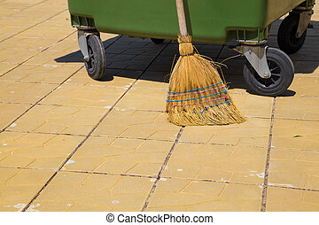 Part of a modern plastic bin with an old straw broom at...